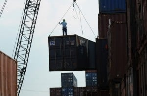 A worker stands on a container at a port in Manila on February 24, 2015.The Philippines on Monday, July 6, 2015, secured another credit-rating upgrade from Japan Credit Rating Agency Ltd. (JCR), which was also the highest that the country has received from major international debt watchers.  AFP PHOTO/TED ALJIBE